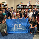 Teachers and students gather around PLC Flag